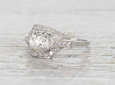 Vintage Edwardian engagement ring made in platinum and centered with an EGL certified 1.50 carat old mine cushion cut diamond. Accented with single cut diamonds. Circa 1910.