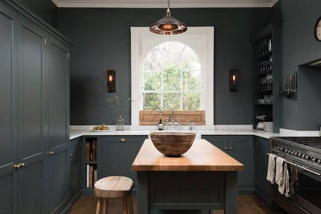 This Shaker kitchen design is by British Design firm DeVOL … painted in moody 'Flint' with honed Carrera marble counters, a butlers sink, 'Bella Brass' fixtures, open storage shelves plus a large pant