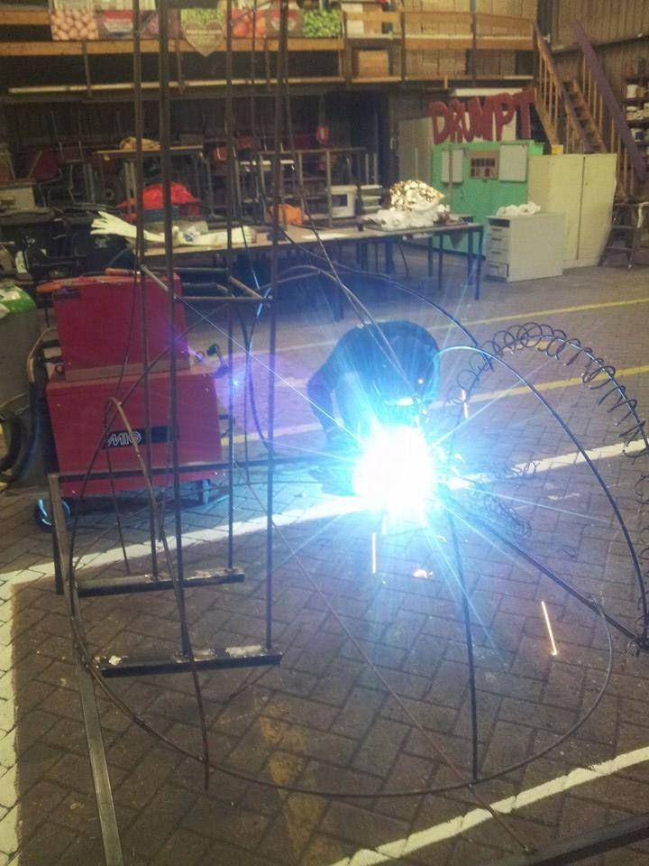 De specialisten van het blauwe licht zijn aan het werk. Zij maken de maquette op ware afmeting door te lassen, te draaien, te vlechten, te buigen en vooral te meten. Een nijptang, een slijptol en een buigapparaat behoren tot de standaarduitrusting van de lasser.