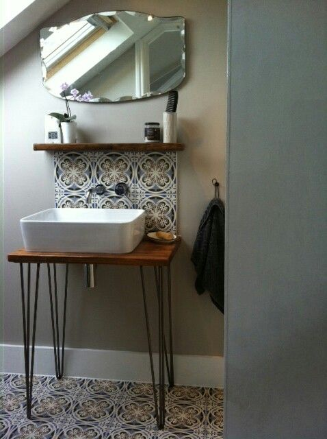 Loft conversion en suite, with counter top basin, wash stand with mid century inspired hairpin legs and bevelled mirror. Fired Earth floor tiles and splashback.