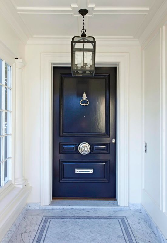 A white marble entrance at the front of  the home leads to a rich navy door with silver hardware. Details such as the  oversized lantern hanging above and elegant molding brighten up the entryway  and give it a clean, interior feel.