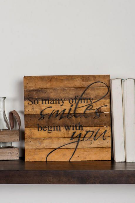 """So many of my smiles begin with you."" This distressed wooden sign with a loving saying says it all! Tell someone how much you love them with the perfect gift to adorn their wall or shelf. <br><br> - 10"" x 10"" <br> - Distressing may vary by piece <br> - Imported<br><br>"