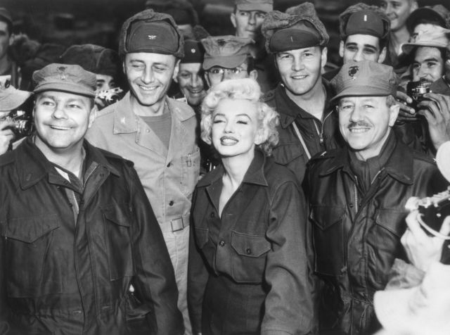 Marilyn Monroe poses with soldiers while on a tour to entertain U.S. troops stationed in South Korea in 1954. Description from wsj.com. I searched for this on bing.com/images