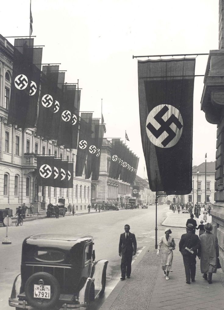 Pre-war Germany. Berlin decorated for the Olympic games, 1936. Hitler was in power by now, and he wanted Germany to look its best: he even went so far as to take down anti-semitic signs and rid the streets of the homeless for the time they hosted the Games.