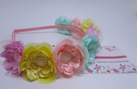 Tiara forrada com fita de cetim, com 8 flores de cetim (rosa, amarela, verde piscina e pêssego).