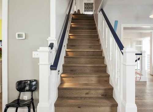 The combination of wooden steps and white banister with blue accents looks relaxed but contemporary. Floors Source: Windermere Real Estate