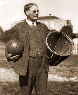 james naismith - holding a ball and a peach basket ... the first basketball equipment.