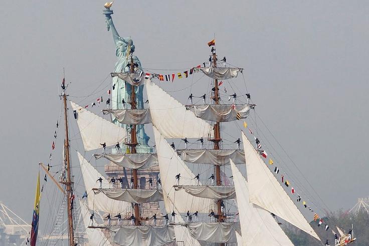 Marinheiros se equilibram nos mastros do navio ARC Gloria. A embarcação de treinamento, com bandeira colombiana, passa em frente à Estátua da Liberdade durante festejos em Nova York