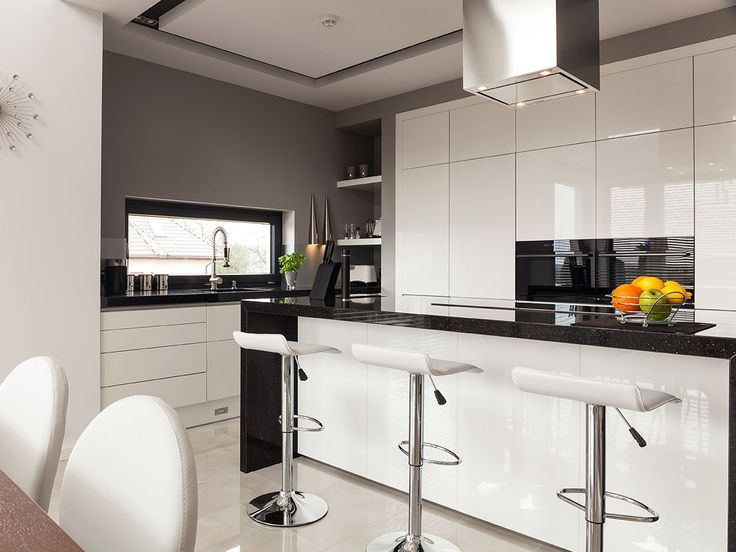 Isle of Capri kitchen: The black granite countertop running to the sides highlights this modern white and grey kitchen.