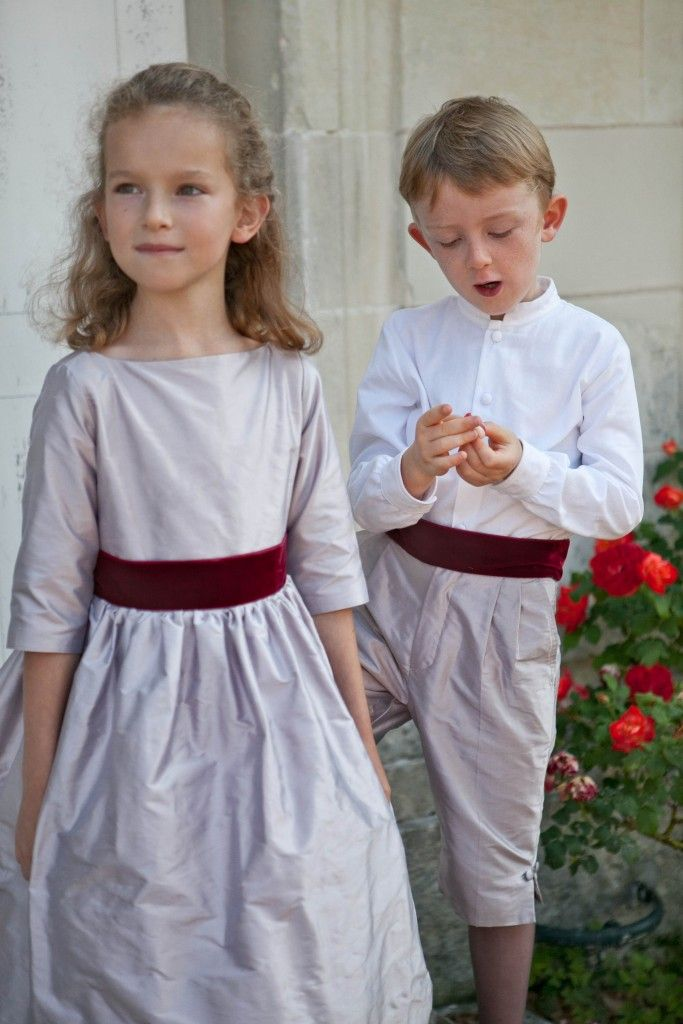 Elise is a pale lilac three-quarter-length sleeve gown with deep red ribbon from Little Eglantine. A matching cape is available and page-boy trousers can be created in the same dupion silk. More at http://absolutely-weddings.co.uk/perfect-bridesmaid-dresses/