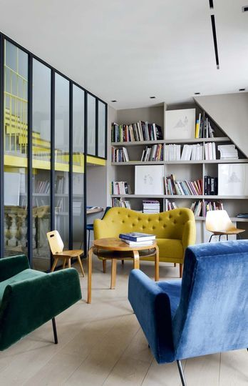 The Internal window does not only bring light; The graphic black lines of the window/wall, the yellow lines of the stairways and the glass, work like a huge modern artwork in the room.
