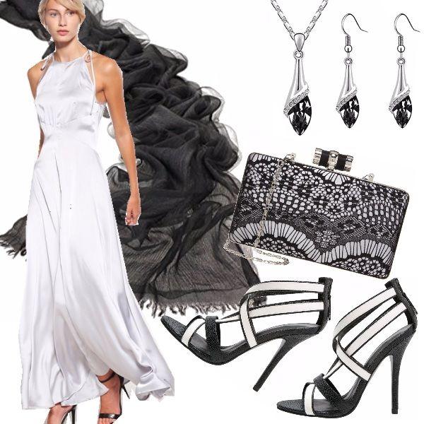 Abito lungo in silver effetto seta adatto a party, cerimonie e serate eleganti, in abbinamento una stola nera in seta per coprire le spalle lasciate nude dall'abito, pochette ricamata, sandali alti bi-color, parure composta da collana e orecchini.
