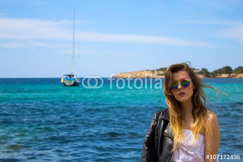 Pretty girl at the turquoise seaside with boat and sea coast