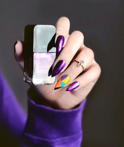 Diseño de uñas color morado y una uña de colores maranja azul y amarillo