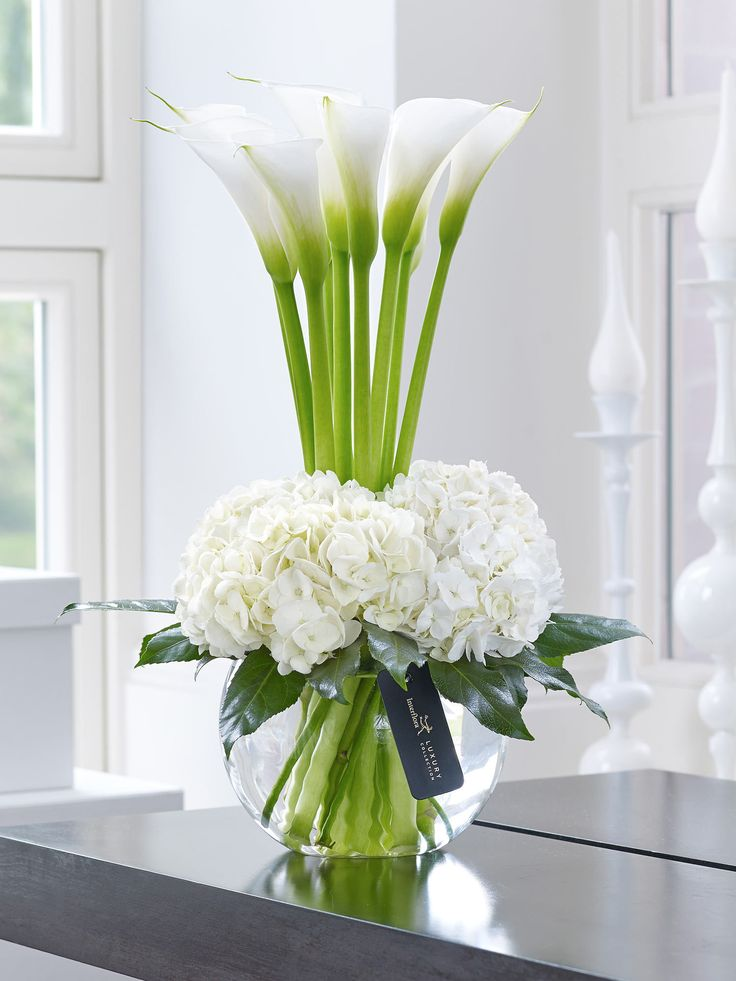 This contemporary designer arrangement is right on trend. We've chosen ultra-fashionable calla lilies in pristine white and created a surround of sumptuous hydrangea blooms with their richly textured flowers. The contrast of smooth elegance and delicate detail is just glorious.<br /><br />Featuring white Snowball hydrangea and white Avalanche calla lilies with aralia leaves and lily grass, expertly arranged in a swirl glass globe and finished with luxury gold and black gift wrapping for…