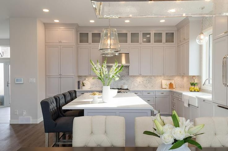 Four black tufted wingback counter stools sit at a white quartz countertop accenting a gray island lit by two seeded glass pendants in this welcoming light gray l-shaped kitchen.
