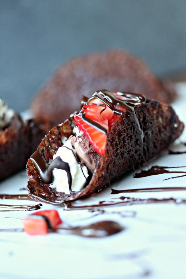 Chocolate Tacos are filled with delicious macerated strawberries. Topped with decadent whipped cream.