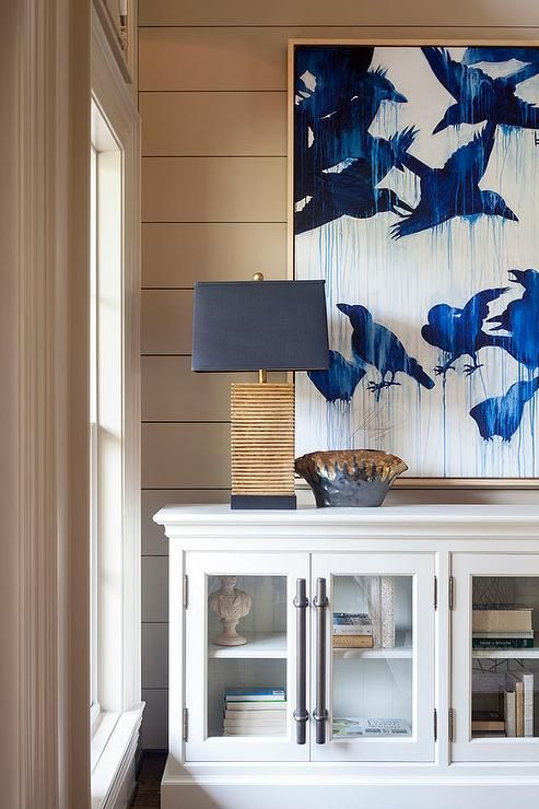 Stunning blue and beige foyer boasts beige shiplap walls holding a gold framed indigo blue birds panting over a white glass front low casement cabinet illuminated by a gold table lamp positioned beside a window.