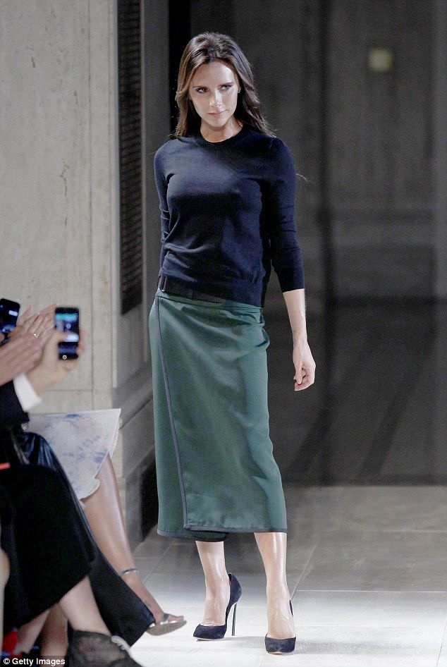 Owning it: Victoria walked down the runway at the end of her show wearing a green midi ski...