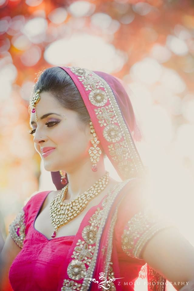 Traditional Indian bride wearing pink bridal lehenga and jewellery