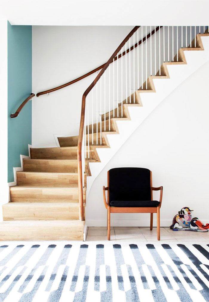 Winding staircase in foyer with single black chair and one blue statement wall