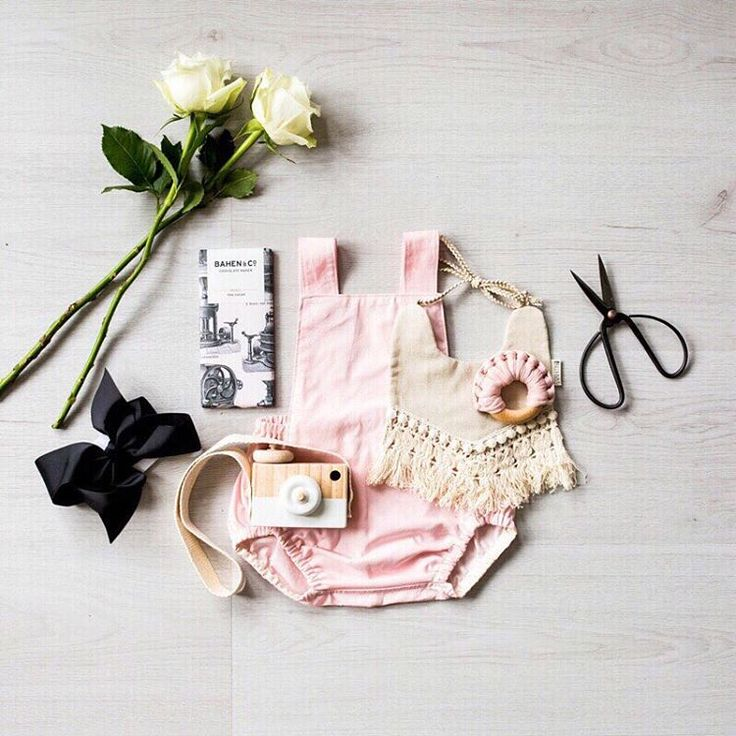 Our baby hamper box 'Little Harmony' in a flatlay.    Baby hamper featuring romper, large bow headband, bib, chocolate, wooden camera and a teether. #babygifts