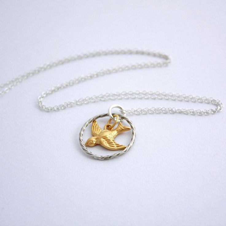 Greta Necklace. Gold swallow charm and a sterling silver circle.