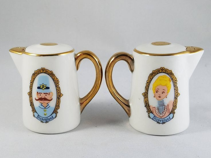 For sale is an adorable pair of Disneyland salt and pepper shakers. This pair of ceramic salt and pepper shakes are a vintage Disneyland souvenir, with a prince and princess represented on one side, and a castle on the other side. They are in the shape of a teapot, with gold accents.  These shakers stand approximately 2 tall and are 2 wide.  They are in good vintage condition with few signs of wear, and both shakers have the original plastic stoppers in the bottom.
