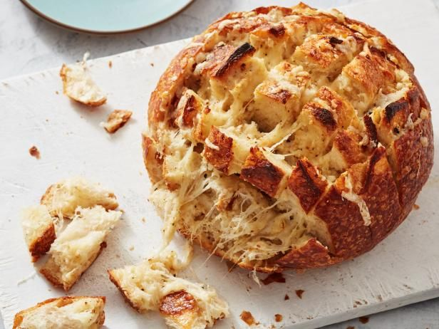 Roasted Garlic and Four-Cheese Pull-Apart Bread Recipe from Food Network, Ree Drummond   party, appetizer, dinner, brunch, garlic, olive oil, kosher salt, black pepper, mozzarella, fontina, parmesan, romano, chives, crushed red pepper flakes, artisan loaf or sourdough loaf, salted butter