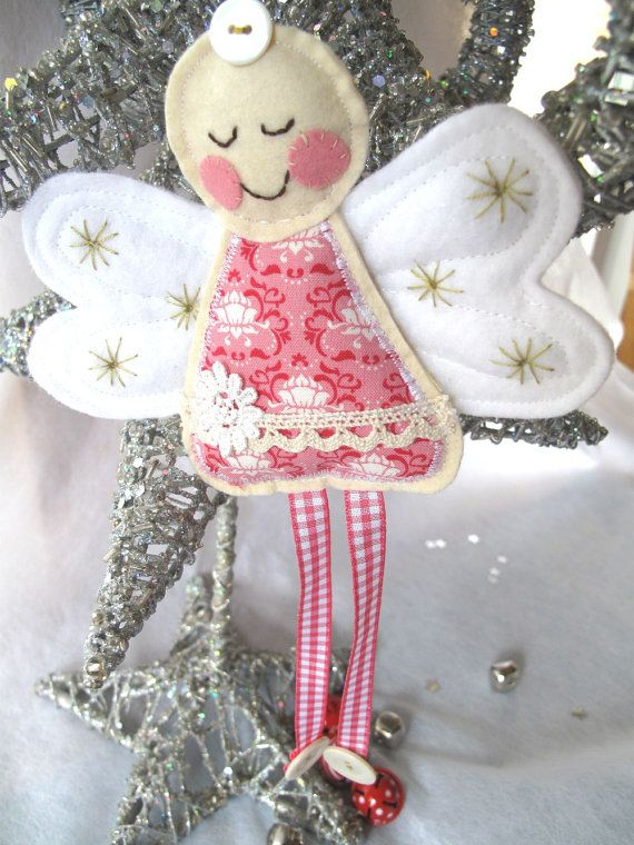 """""""A cream felt stuffed body and face with hand stitched features and pinkest cheeks. The white wings are quilted and then finished with antique yellow stars. Pink Tilda fabric with lace and flower trim.  Long pink gingham ribbon legs with button feet to hang charismatically."""""""