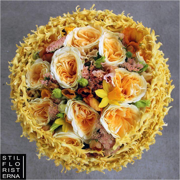 Aprikosgul brudbukett i vårkänsla, med rosor, japansk ranunkel och trådade hyacinter.