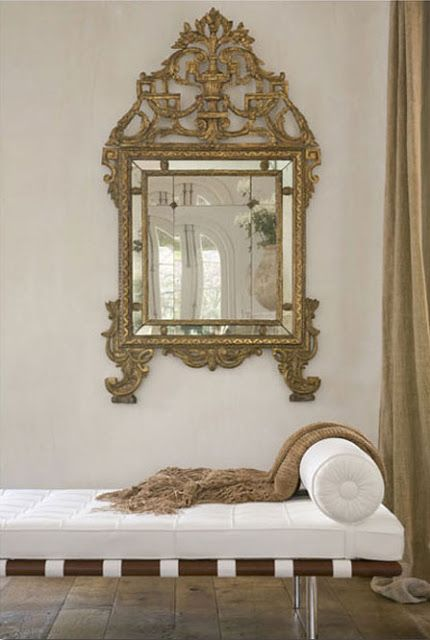 Gilt meets modern: ornate statement mirror over contemporary white chaise.