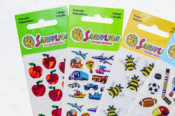 5 sealed packs of Sandylion stickers, 1990s. In the lot: - Prismatic red apples - Prismatic vehicles - Fuzzy bees - Sports collection (piece ripped from top of packaging but still sealed) - Camping collection  ***** Looking for more great vintage stickers? We have more here (and many