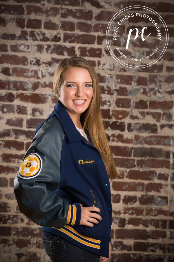 high school senior pics sports pose girls in sports letterman jacket soccer