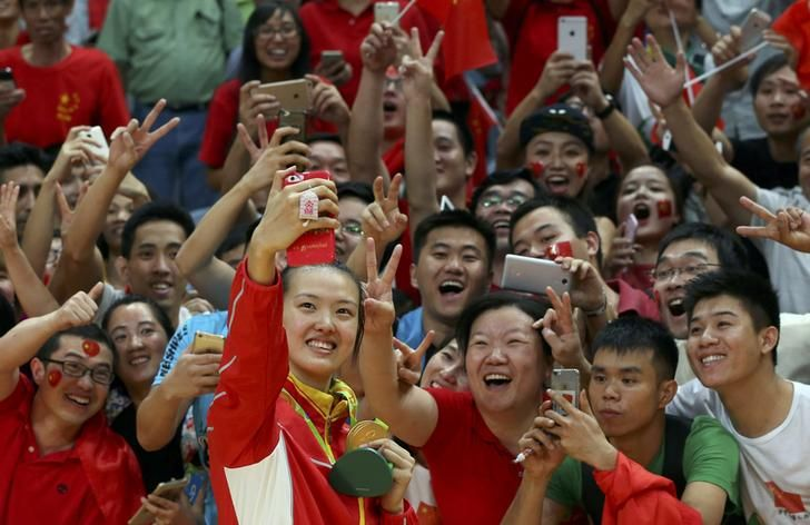 2016 Rio Olympics - Volleyball - Women's Victory Ceremony - Maracanazinho - Rio de Janeiro, Brazil - 21/08/2016. Gold medalist Zhang Changning (CHN) of China takes a selfie with supporters. REUTERS/Yves Herman