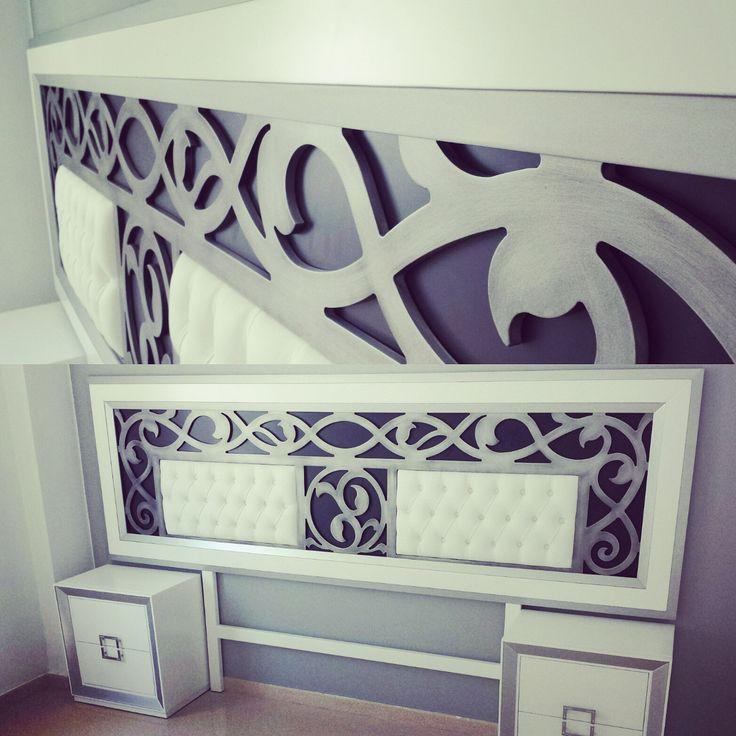 Dormitorio en color blanco y plata con capitoné en el cabecero tapizado de polipiel blanca y dos mesitas de noche.