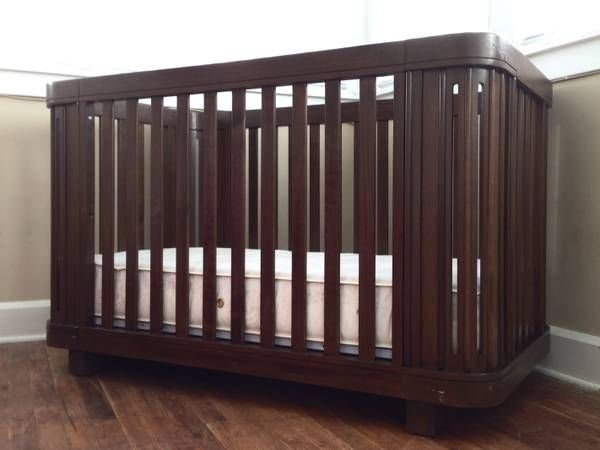 "Baby Italia Eco Babi Crib in ""Coffee Bean"" This is a beautiful midcentury modern style, dark wood, eco-friendly crib. It's made of solid (thick), durable pine wood, has unique rounded edges and has a no-VOC, non-toxic finish. It has a mattress platform that raises & lowers to 3 different heights as baby grows. It also comes with a toddler bed conversion kit. Besides that it is in excellent condition. Craigslist"