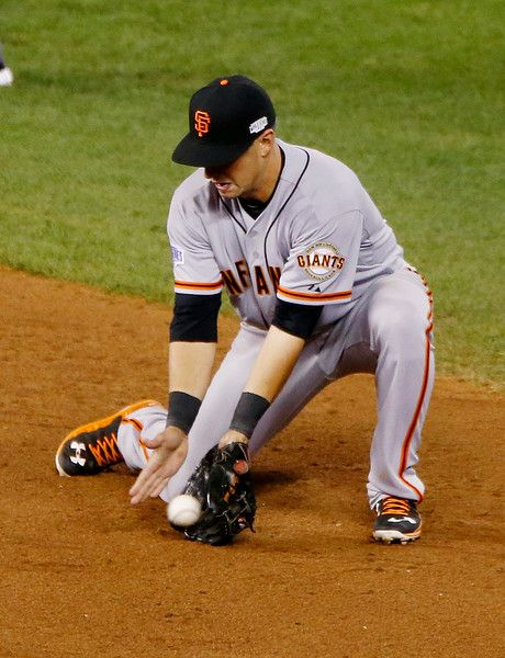 San Francisco Giants' Joe Panik (12) fields the ball in the ninth inning of Game 1 of baseball's World Series against the Kansas City Royals Salvador Perez (13) at Kauffman Stadium in Kansas City, Mo., on Tuesday, Oct. 21, 2014. (Josie Lepe/Bay Area News Group)