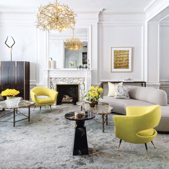 """Un salon gris et or avec des meubles aux formes arrondies comme ce superbe canapé gris """"Serpentine sofa"""", les fauteuils italiens des années 60 et les tables basses en onyx et bronze."""