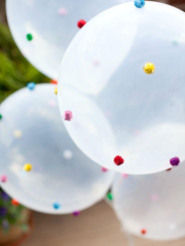Ballonnen versierd met pompoms. Pas de kleur toe van je thema en je hebt superleuke decoratie.