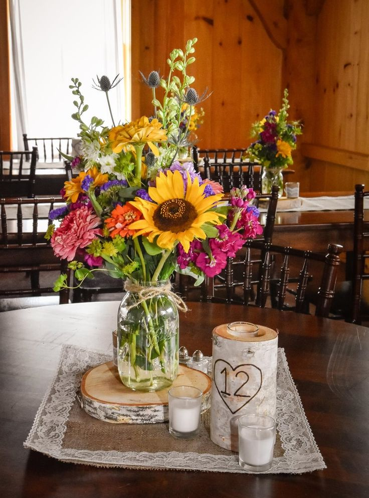 we love these country wildflower centerpieces featuring sunflowers, stock, zinnias and thistle in mason jars. Designed by Jen-Mor Florist in Dover, Delaware. www.jenmor.com