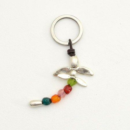 Llavero libélula de colores, con tira de cuero y abalorios zamak. La cola está compuesta por piedras de resina en distintos colores. PRECIO: 9 €