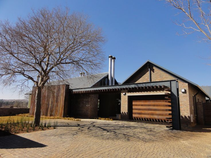 House Uys in Pretoria, South Africa. This is a single storey home built in a farming estate and located with views over the neighboring golf course, enjoying the best of both worlds. A steel I-beam and wood structure, reminiscent of an elongated spine, frames the western facade from the street, while leading the eye to the front door. Completed 2010 by Mathews and Associates Architects. Photo courtesy of Pieter Mathews.