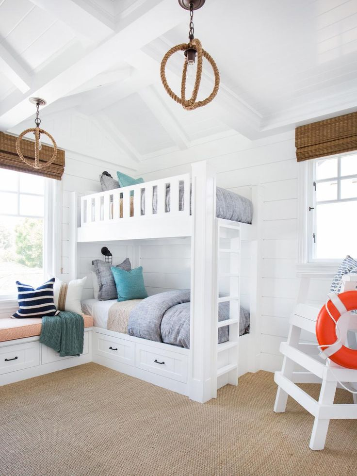Built-in bunk beds are functional and adorable in this coastal kids' room. Crisp white shiplap walls add a charming touch and keep the space looking bright and fresh.