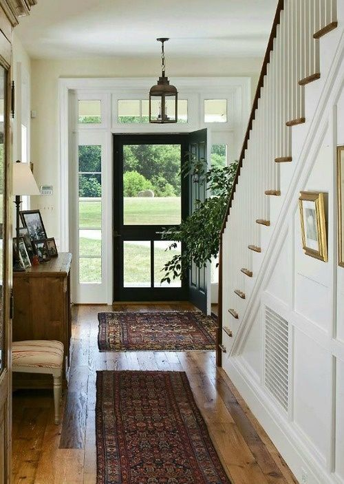 Farmhouse touches, iron lanterns and Persian runners in the open entryway.