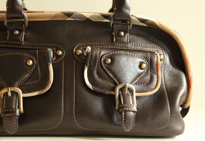 Burberry - Schoudertas - Handtas - Bowling Bag  Een middelgrote schoudertas/handtas gemaakt van donker bruin leer. De tas is afgewerkt met oud goudkleurig hardware. Het model is ruim casual en handig voor alledaagse activiteiten. Binnenin 1 grotere vak en meerdere zijvakjes waarvan er eentje ook een ritssluiting heeft. De tas sluit met een rits. De tas toont weinig gebruikssporen zowel binnen als buiten en in het algemeen verkeert in zeer goede gebruikte staat. Afmeting: 38 cm x 20 cm x 21…