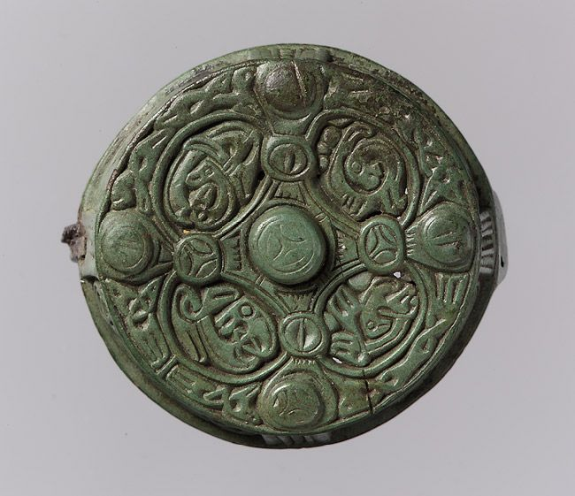 Round Box Brooch, 700–900 Viking; Made in Gotland, Sweden Copper alloy. A menagerie of tiny animals inhabits the interlace patterns on this round brooch. The four oval compartments on the top show beasts with round eyes, open jaws, claw feet, and intricately entwined bodies. Known as a box brooch because it was used as a container for small objects, it would have been worn by a Viking woman on the island of Gotland to secure her shawl at the collar.