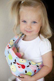 Criança brincando de boneca com sling aprendem sobre a maternidade e paternidade com amor.