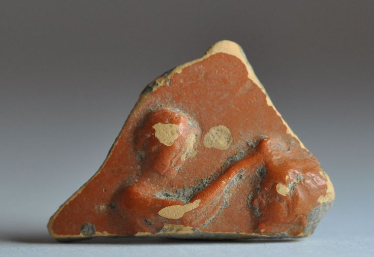 Theater mask on arretine ware Samian ware shard with man holding theater mask with hand, 1st century A.D. 3.3 cm long. Private collection