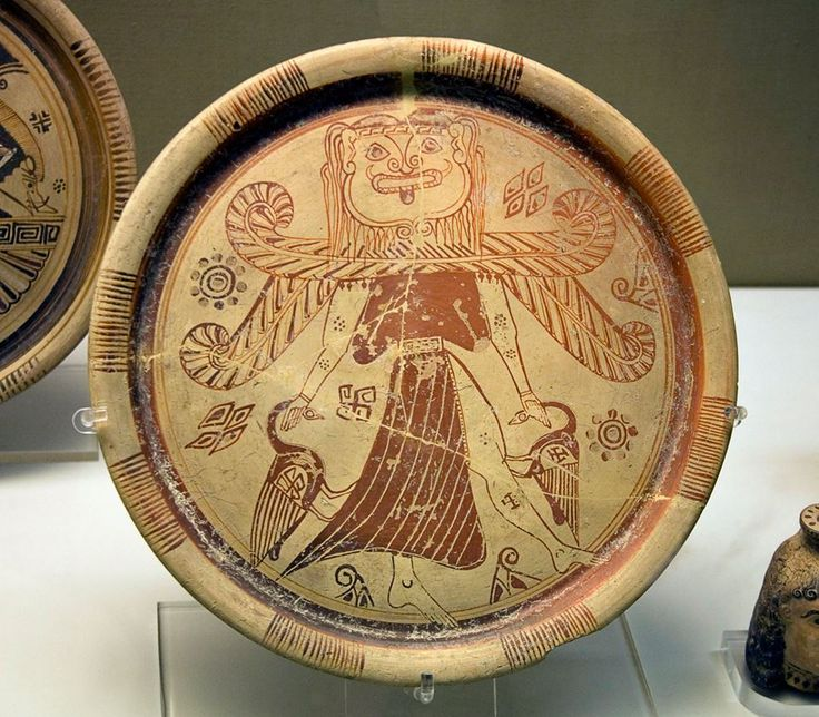 A Gorgon-headed mistress of the animals. Pottery plate showing a winged goddess with a Gorgon's head wearing a split skirt and holding a bird in each hand, type of the Potnia Theron. From Kamiros, Rhodes. British Museum